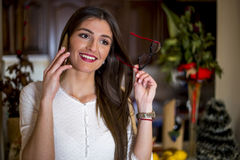 Beautiful woman talking on a phone at home Royalty Free Stock Photo