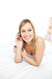 Beautiful woman talking on phone lying on her bed Royalty Free Stock Images
