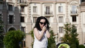 Beautiful woman talking on the phone outdoors. A young mother is talking on the street. She smiles, and you can see in. The background a little child in a stock video