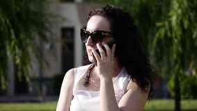Beautiful woman talking on the phone outdoors. A young mother is talking on the street. A woman with glasses. Slow. Beautiful woman talking on the phone outdoors stock footage