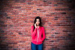 Beautiful woman talking on the phone over brick wall Royalty Free Stock Image