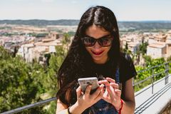 Beautiful woman talking on the phone from a panoramic view of the charming city royalty free stock image
