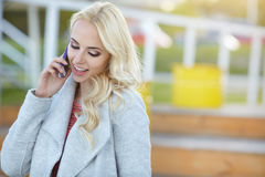 Beautiful woman  talking on the phone on the street Stock Images