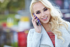 Beautiful woman  talking on the phone on the street Stock Photography