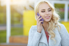 Beautiful woman  talking on the phone on the street Royalty Free Stock Photos