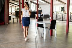 Beautiful Woman Talking On Phone Walking In Office. Portrait Of Stylish Smiling Business Woman In Fashionable Clothes Royalty Free Stock Photos
