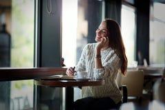 Beautiful woman talking on phone and writing stock photo