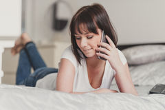 Beautiful woman talking on smartphone in her bedroom Royalty Free Stock Photo