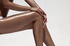 Beautiful woman tan legs. Against white wall. Royalty Free Stock Photos
