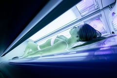 Beautiful woman tanning in solarium Stock Photos