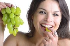 Beautiful woman. Tasting grapes, smile Royalty Free Stock Photos