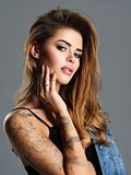 Beautiful sexy girl with a tattoo on the body. Beautiful  woman  with a tattoo on the hand. Portrait of young adult sexy woman with brown hair Stock Photos