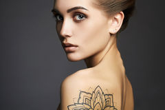 Beautiful woman with tattoo. Young blond woman with tattoo.Beautiful blonde Girl with make-up.fashion portrait royalty free stock photography