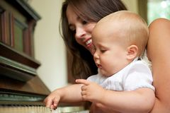 Beautiful woman teaching baby to play piano Royalty Free Stock Images