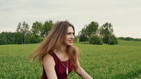 Beautiful woman teases her lover running away in a field, he chases. Happy lovers have fun. Slow mo, steadicam shot stock video