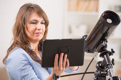 Beautiful woman with telescope and tablet Royalty Free Stock Image