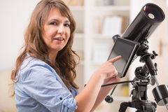 Beautiful woman with telescope and tablet Stock Image