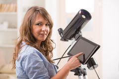 Beautiful woman with telescope and tablet Stock Photography
