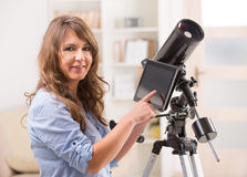 Beautiful woman with telescope and tablet Royalty Free Stock Photos