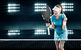 Beautiful woman tennis player celebrating flawless victory. Beautiful girl tennis player with a racket on dark background wiht lights celebrating flawless Stock Images