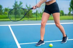 Beautiful woman with tennis racket on tennis court. Beautiful woman with tennis racket playing tennis on blue court royalty free stock images