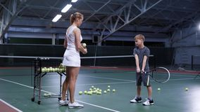Beautiful woman tennis trainer teaching little boy how to play tennis. She throwing the ball to him stock footage