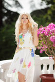Beautiful woman on the terrace with pink flowers. Slender,beautiful blonde with long curly hair and gray eyes,a light transparent white dress with a white belt,a royalty free stock photos