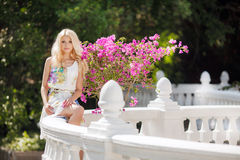 Beautiful woman on the terrace with pink flowers Stock Photos
