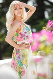 Beautiful woman on the terrace with pink flowers Stock Image