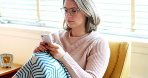 Beautiful woman text messaging on mobile phone in living room. At home stock footage