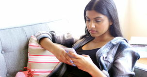 Beautiful woman text messaging on mobile phone in living room. At home stock video