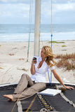 Beautiful Woman Texting On Boat At The Beach Stock Photos