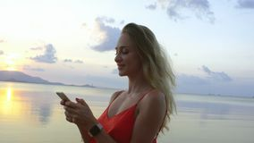 Beautiful woman texting on smartphone on the beach. Happy tourist using modern device and smiling stock video footage