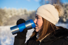 Beautiful woman with thermal mug in winter forest Royalty Free Stock Photo