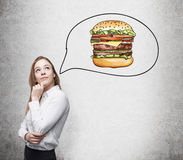 A beautiful woman is thinking about burger. A fast food concept. Royalty Free Stock Images