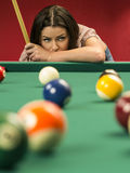 Beautiful woman thinking about her next pool shot. Photo of a beautiful brunette at the edge of a billiards table holding a pool cue and wondering about her next Royalty Free Stock Image