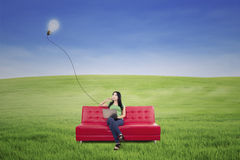 Beautiful woman thinking on red sofa under lamp outdoor Royalty Free Stock Photos