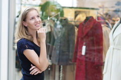 Beautiful woman thinking about shopping. Beautiful woman in the mall, Thinks about purchases Royalty Free Stock Image