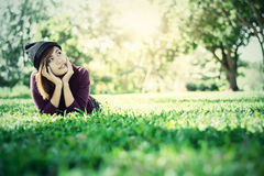 Beautiful woman thinking something on green grass Stock Photography