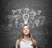 Beautiful woman is thinking about undiscovered issues. Question marks and a light bulb are drawn on the black chalkboard beh Royalty Free Stock Images