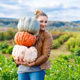 Beautiful woman with three huge pumpkins on farm Royalty Free Stock Photos