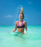 Beautiful woman throw back hair from the water Royalty Free Stock Image