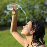 Beautiful woman throwing herself water from a plastic bottle Royalty Free Stock Photo