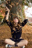 Beautiful Woman Throwing Leaves. An image of a pretty young woman smiling as she throws leaves up in the air Royalty Free Stock Photography