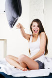 Beautiful woman throwing a pillow Stock Photos