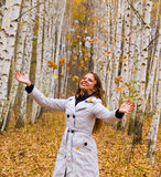 Beautiful woman throws up autumn leaves Stock Images