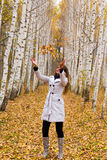 Beautiful woman throws up autumn leaves Stock Photos