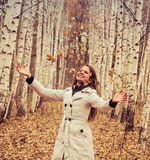 Beautiful woman throws up autumn leaves Royalty Free Stock Images