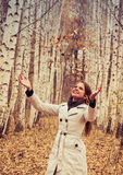 Beautiful woman throws up autumn leaves Royalty Free Stock Photography