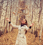 Beautiful woman throws up autumn leaves royalty free stock image